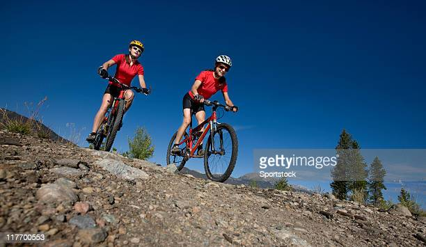 Two Young Adults Riding Mountain Bikes