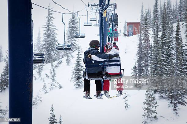 Two young adults smile while sitting on a double chairlift at a ski resort in Idaho.