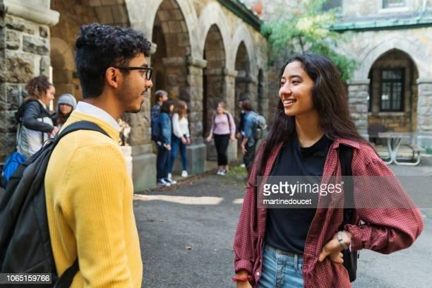 """twee jonge volwassenen studenten chatten in de ingang van het college. - """"martine doucet"""" or martinedoucet stockfoto's en -beelden"""