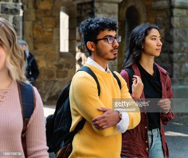 "two young adults students listening in college entrance. - ""martine doucet"" or martinedoucet stock pictures, royalty-free photos & images"