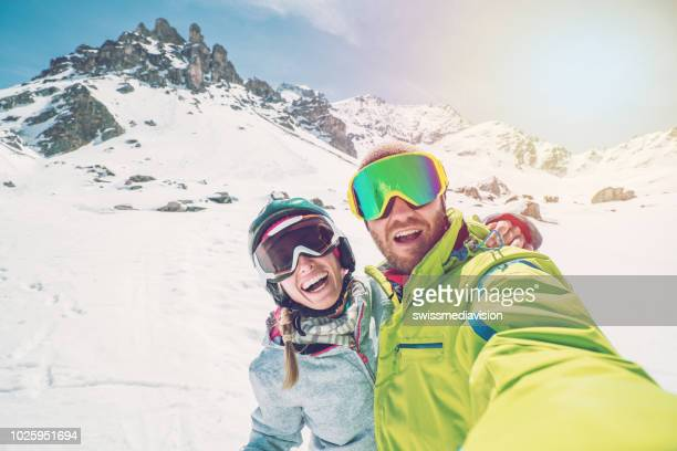 two young adults taking selfie from ski slopes in switzerland, ski holidays of couple tourist enjoying swiss alps and vacations concept - skiing stock pictures, royalty-free photos & images