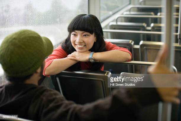 Two young adults talking on train