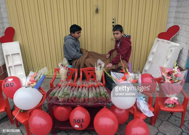 Two young Afghan vendors warm themselves as they wait for customers to sell heartshaped balloons on Valentine's Day in Kabul on February 14 2018 In...
