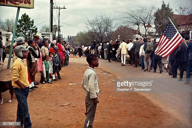 Two young African American boys stand in the street with other onlookers watch the Selma to Montgomery civil rights marchers go by on March 25 1965...