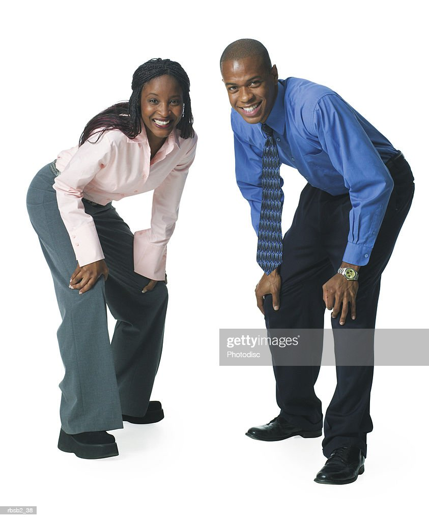 two young african american business people crouch down and playfully smile : Foto de stock