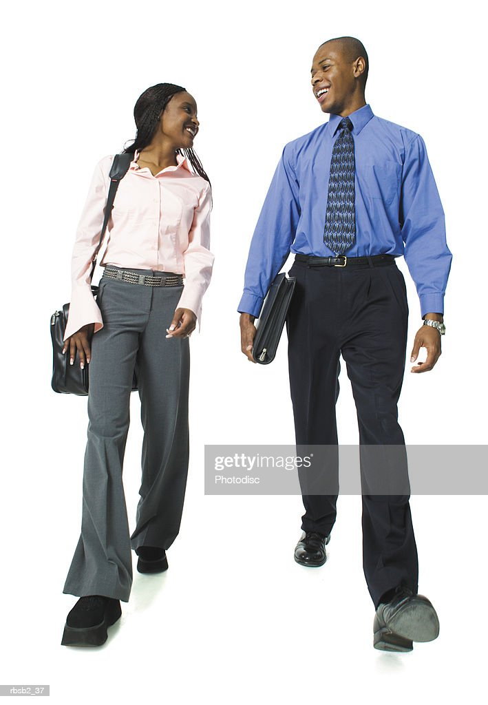 two young african american business people walk along having a conversation : Foto de stock