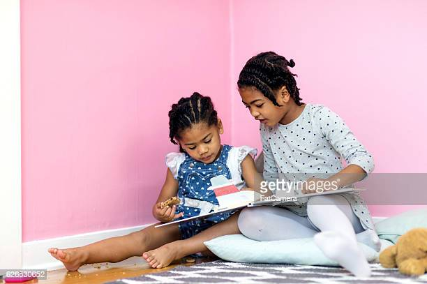 Two young African American sisters reading a book together