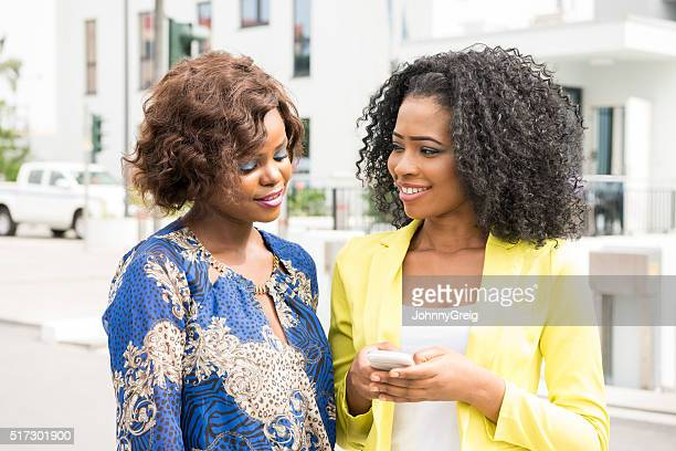 Two young African women with cell phone, smiling