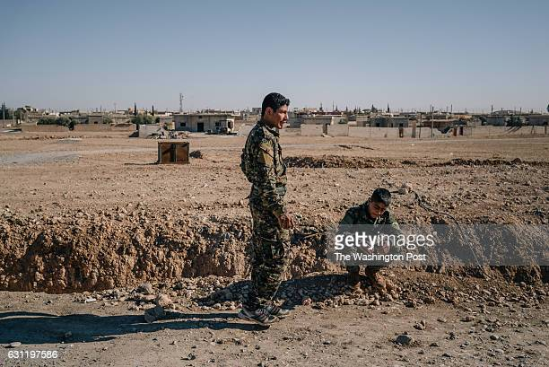 Two young Arab members of the YPG who claim they joined the group when their hometown Manbij was recaptured from ISIS stand outside a base in Ain Issa