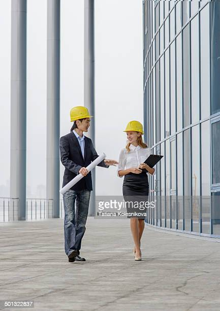 Two young architects walking on construction site