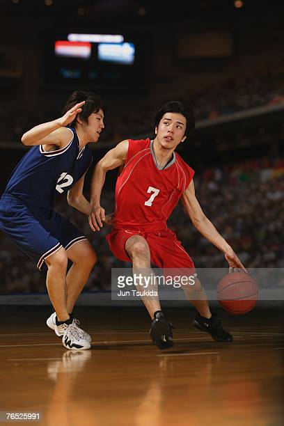 Two young Asian basketball players competing