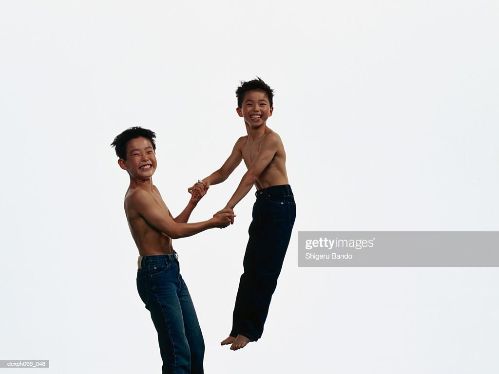 Two young Asian boys in jeans only, jumping in mid-air : Stock Photo