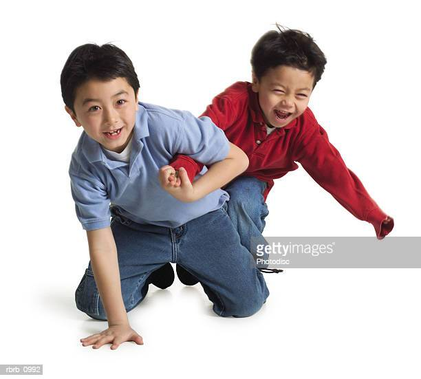 two young asian brothers kneel down and play together
