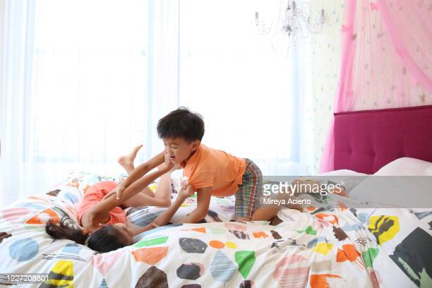 two young asian children wearing summer clothes, playfight on the bed in a colorful, brightly lit bedroom. - girl wrestling stock pictures, royalty-free photos & images
