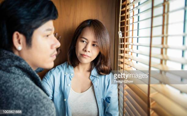 Two young asian couple standing face off from each other