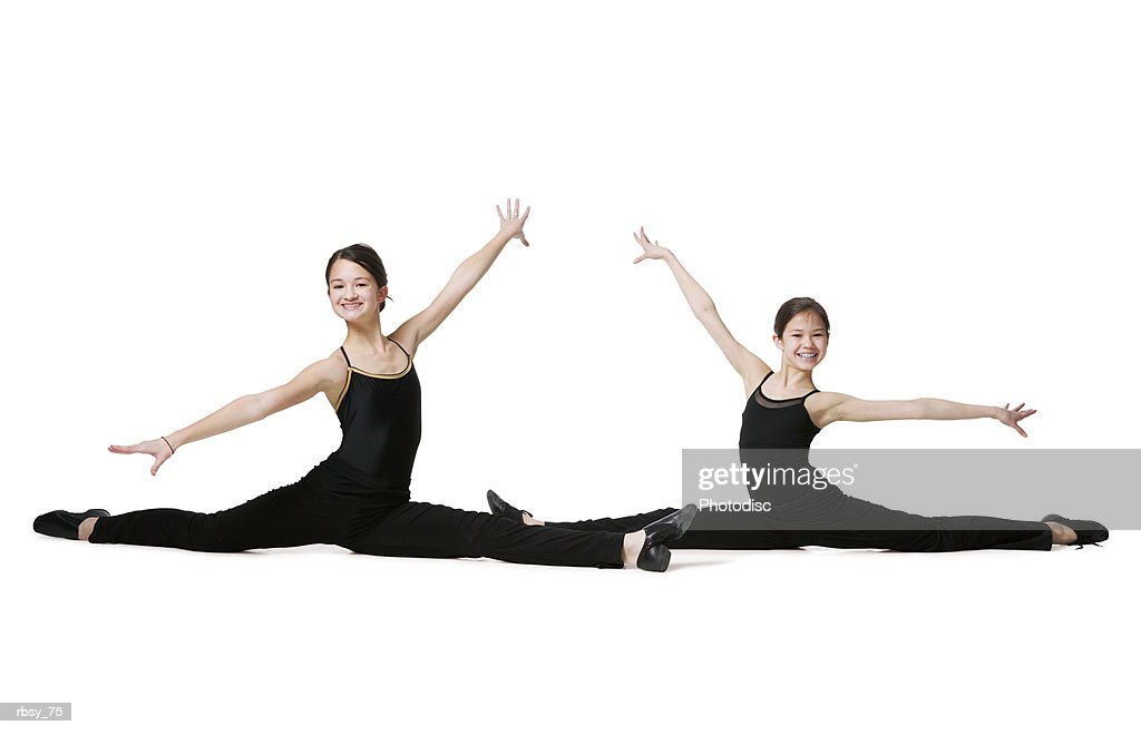 two young asian sisters dressed in black leotards stretch out in a dance pose and smile : Foto de stock
