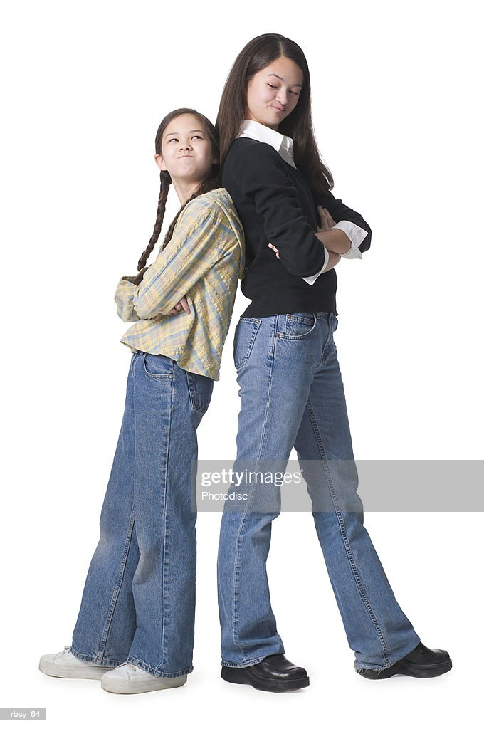two young asian sisters fold their arms and stand back to back with their arms folded and looking upset : Foto de stock