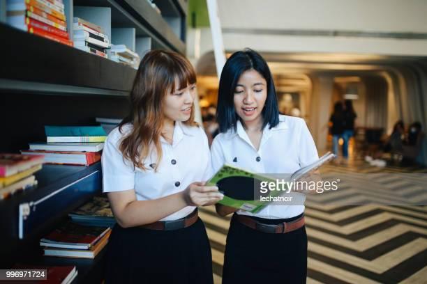 Zwei junge asiatische Studenten in Uniformen im Gespräch in der Campusbibliothek nach Klassen