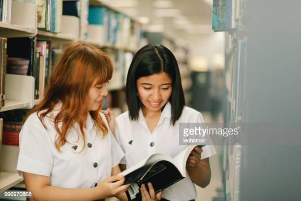 Zwei junge asiatische Studenten auf der Suche nach Büchern in der Bibliothek
