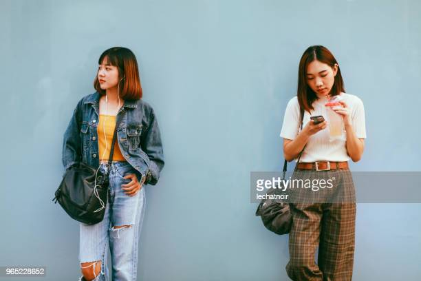 two young asian women in bangkok downtown district, taking a break, texting on the cellphone, waiting - big bobs stock photos and pictures