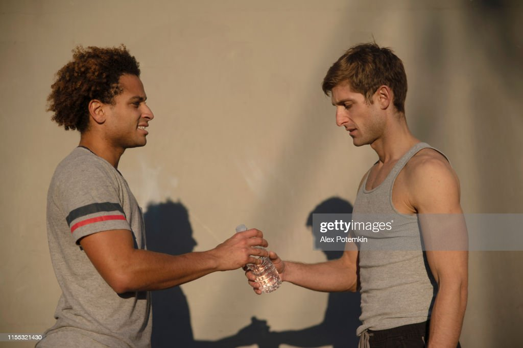 Two young athletes drinking bottled water : Stock Photo