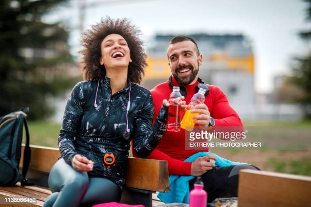 two young athletes in sports clothing putting their energy drink bottles together and laughing while sitting on a bench in a public park - energy drink stock pictures, royalty-free photos & images
