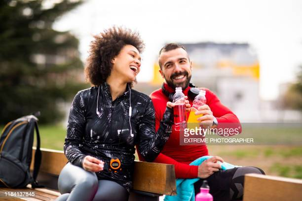 two young athletes in sports clothing putting their energy drink bottles together while sitting on a bench in a public park - energy drink stock pictures, royalty-free photos & images
