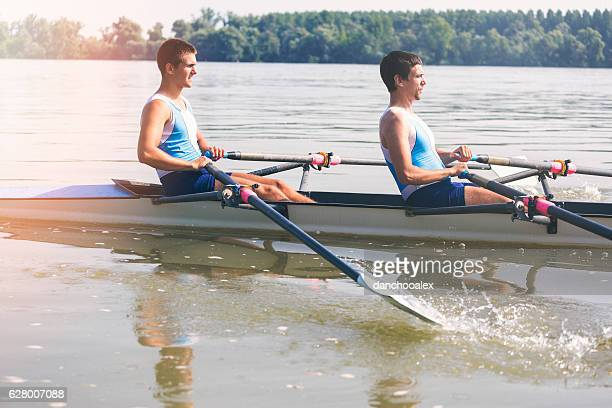 Two young athletes rowing on the river