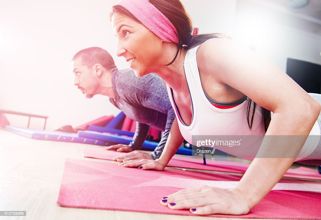 Two young athletes warming up and exercising push-ups in gym : Stock Photo