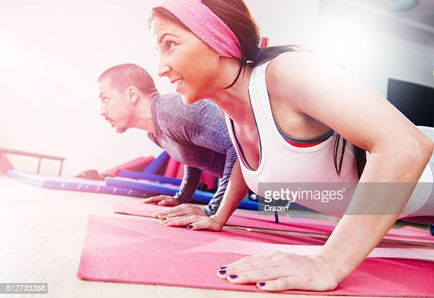 two young athletes warming up and exercising push-ups in gym - circuit training stock photos and pictures