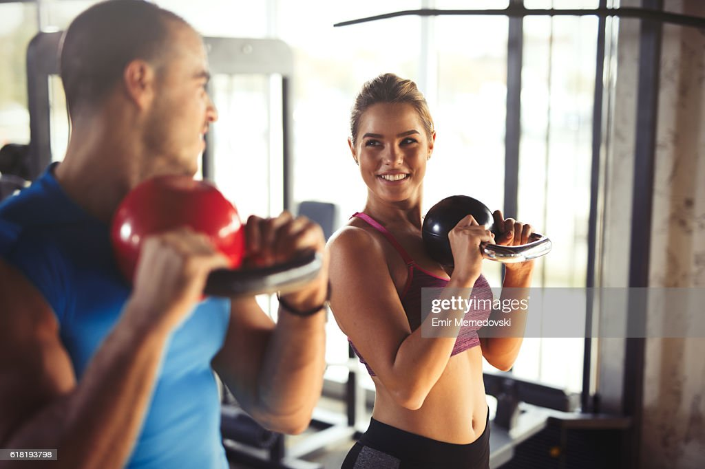 Two young athletic people doing kettlebell exercises at gym. : Foto stock