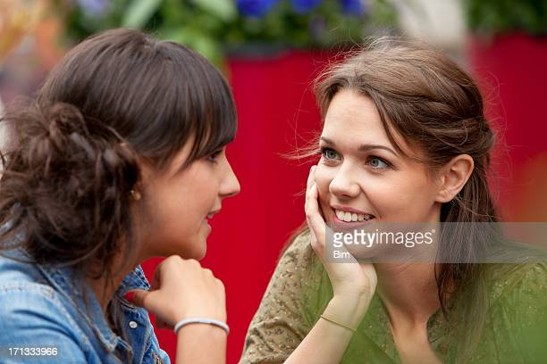 Two young  attractive women talking in street cafe