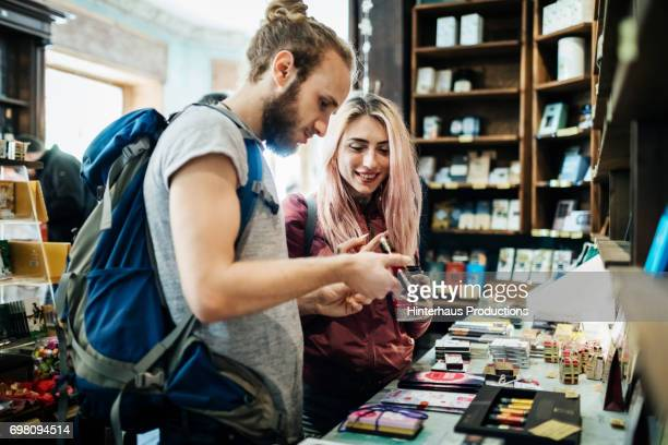 Two Young Backpackers Exploring A Store Together
