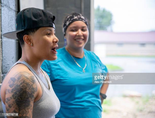 Two young beautiful Latino women resting between workouts, talking and laughing at the gym