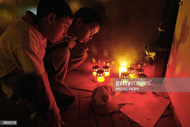 Two young Benfica supporters observe candles in the Luz Stadium at Lisbon 26 January 2004 in honour of Hungarian soccer player Miklos Feher who died...