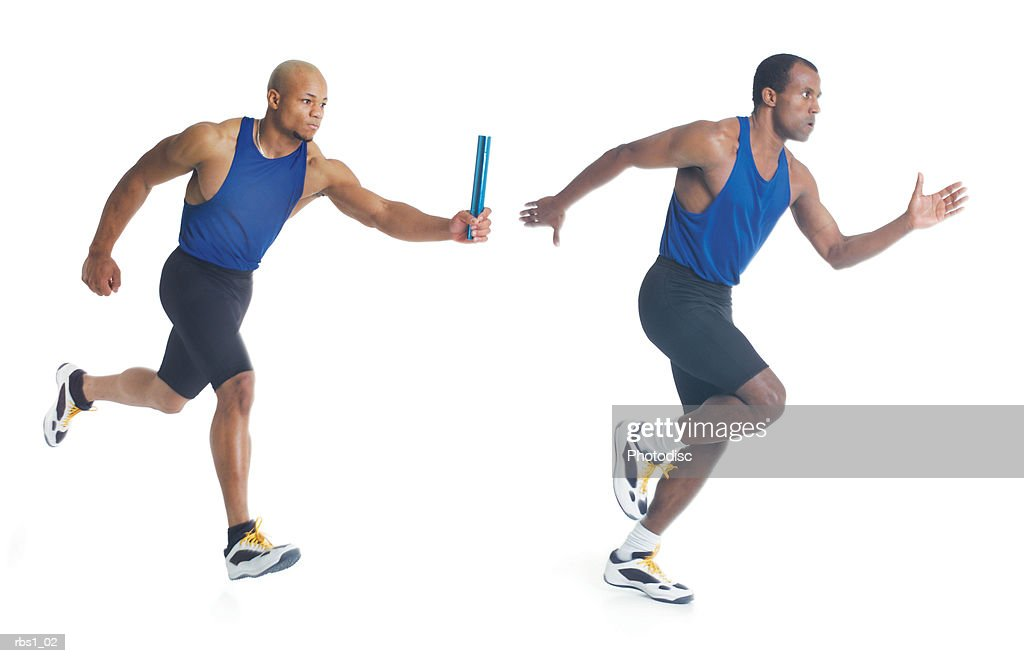 two young black men in blue tank tops are running a race as they pass a blue baton : Foto de stock