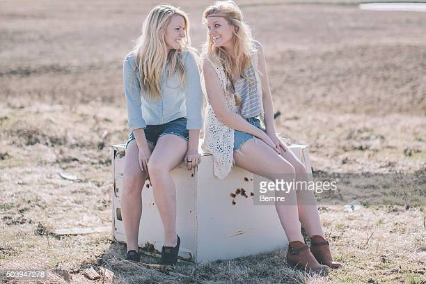 Two Young Blonde Females Sitting in Field