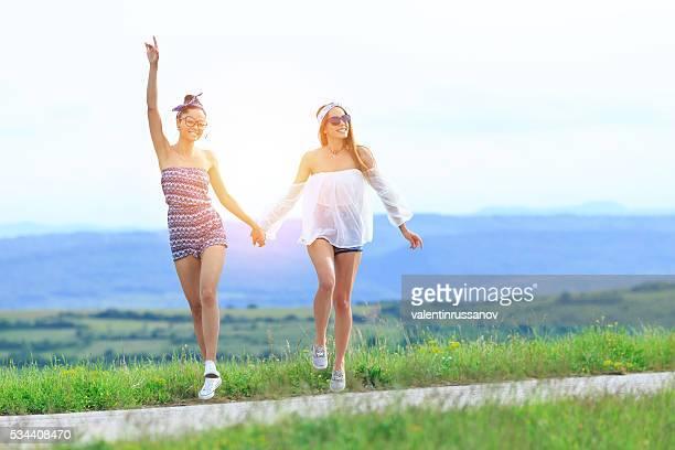 Two young boho women having fun on the road