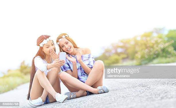 Two young boho women sitting on the road with smartphone