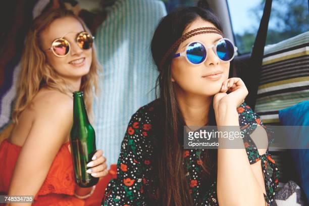 Two young boho women wearing sunglasses in recreational van