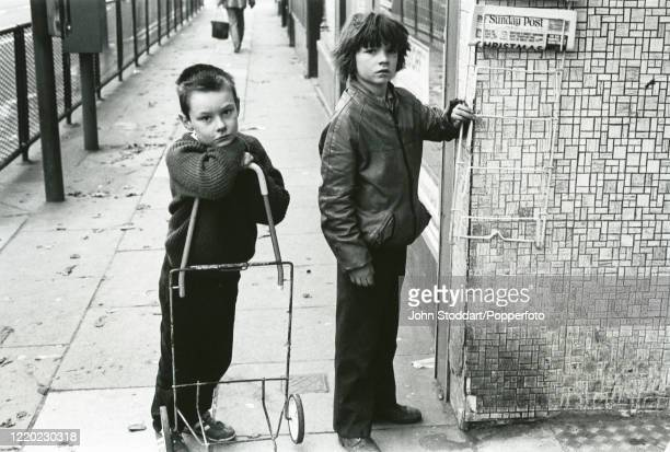 Two young boys after finishing their paper round on a Sunday morning in Liverpool, circa 1982. The 1980s saw the City of Liverpool's fortunes sink to...