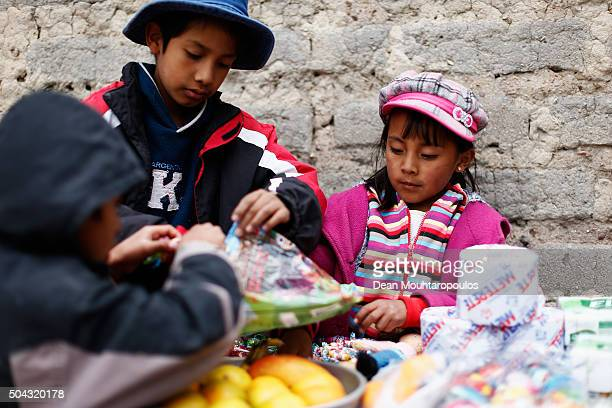 Two young boys and a girl whose family live near the race course set up a market stall selling fruit toys sweets and candys to spectators as day 7...