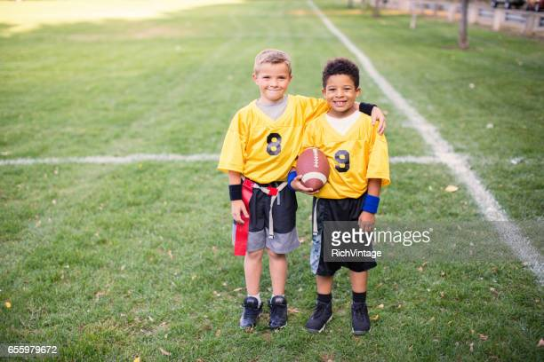 Two Young Boys and Teammates Play Flag Football