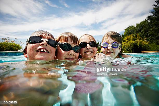 Two young boys and two young girls in pool