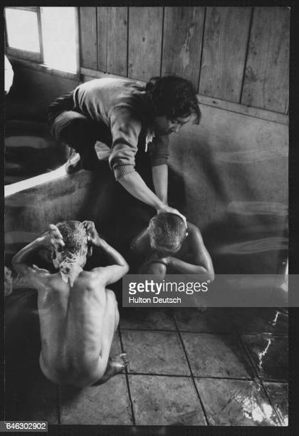 Two young boys are given a bath upon their arrival at the Children's Protective Home which provides both schooling and medical attention for needy...