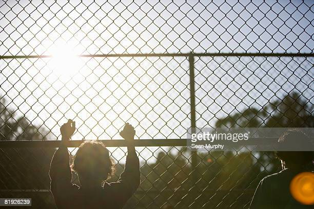 two young boys at a chain-link fence