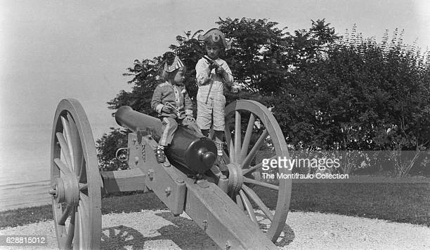 Two young boys both wearing tricorn hats one in a soldier's uniform holding a gun and rifle on top of a large artillary cannon on a wheeled base...