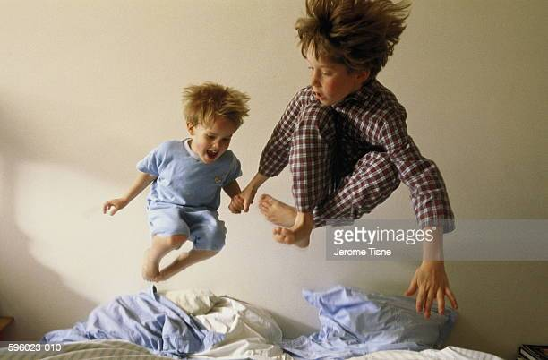 Two young boys (4-9) bouncing on bed