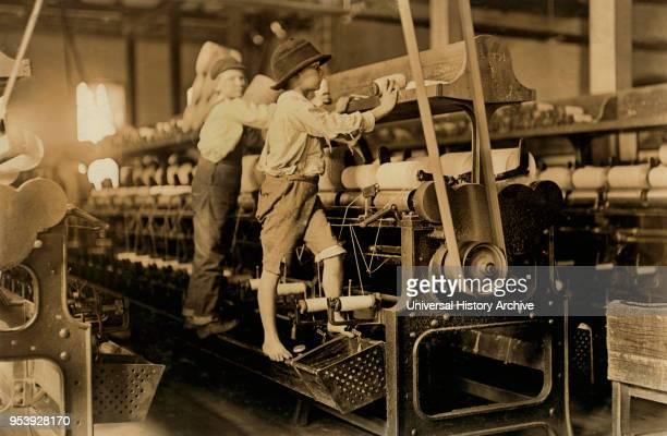 Two Young Boys Climbing on Spinning Frame to Mend Broken Threads and Put Back Empty Bobbins, Bibb Mill No. 1, Macon, Georgia, USA, Lewis Hine for...
