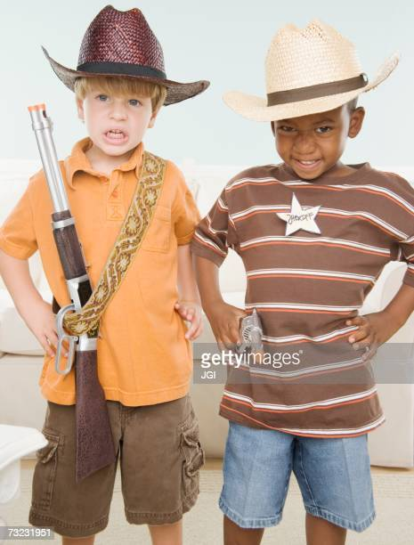 Two young boys dressed up as cowboys indoors